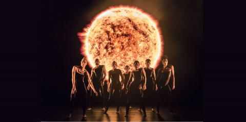 Alexander Whitley Dance Company: 8 Minutes: Dancers standing in front of an enormous projected Sun