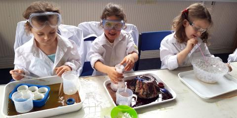 Little Volcanoes Science Club - Three girls in lab coats are sitting doing experiments with bubbles and goo