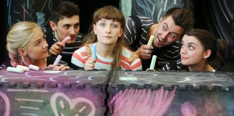 Chit Chat Chalk Show: a company member holding up chalk and staring surprisedly at it, as other company members in the background look on