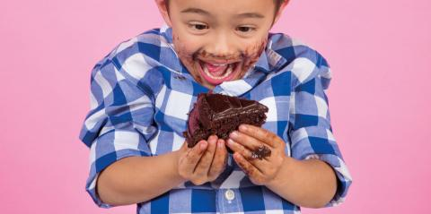 A little boy before a pink background, with a piece of chocolate cake
