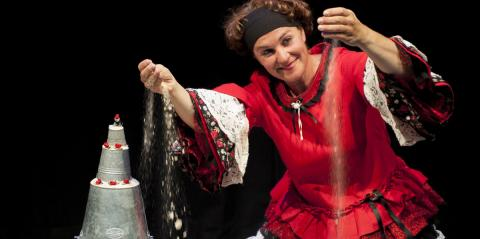 Circles in the Sand: Actor Marlen Vermeulen in a red and black frilly dress, letting sand trickle through her fingers onto the sand covered floor