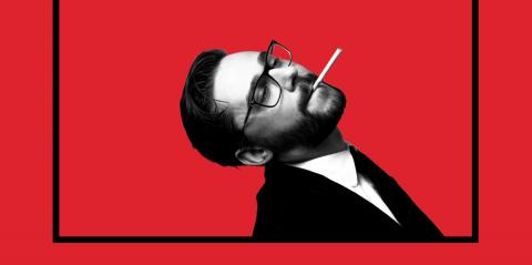 The face young white man with a cigarette on a stark red background