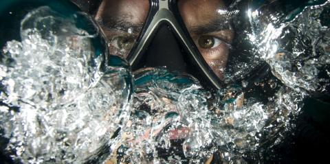 A diver's eyes staring out from the dark behind goggles and bubbles