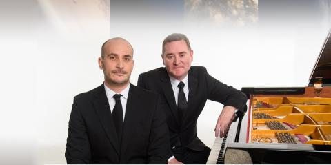 Two pianists sitting in front of a projection of planets