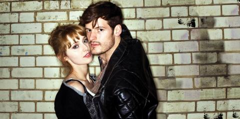 a couple in contemporary clothing hugging in front of a brick wall, brightly lit by a flash