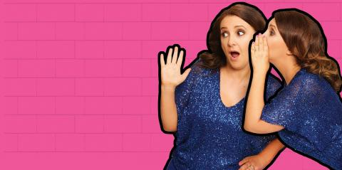 Lucy Porter whispering into the ear of another, shocked-looking, Lucy Porter in front of a bright pink wall