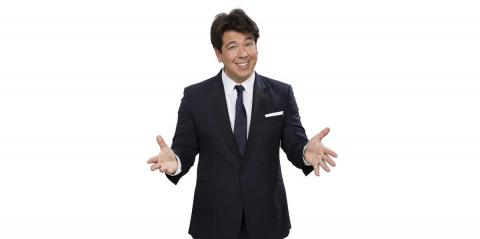 An photo of comedian Michael McIntyre wearing a suit gesturing to the camera.