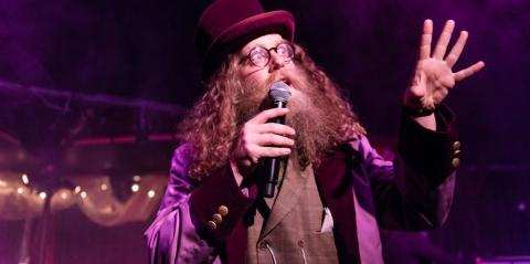 Ben Caplan, in a top hat, gesturing excitedly while talking into a mic