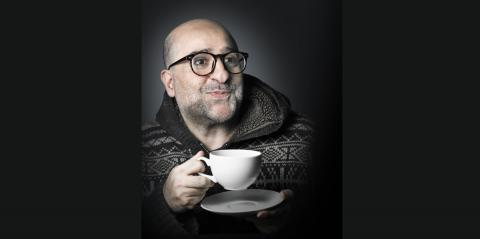 Omid Djalili - wearing a grey sweater, a wry smile on his face and is holding a tea cup
