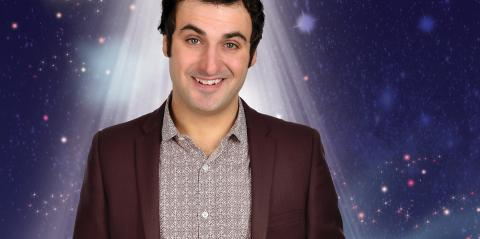 Pub Quiz for Kids: Patrick Monahan smiling in a spotlight