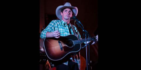 Rich Hall wearing a blue cowboy hat and strumming a guitar looking wearily into the distance