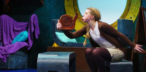 A woman blowing a raspberry to a wooden snail