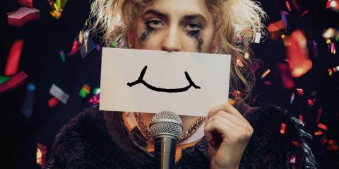 A woman with tear-stained make-up pretending to be happy