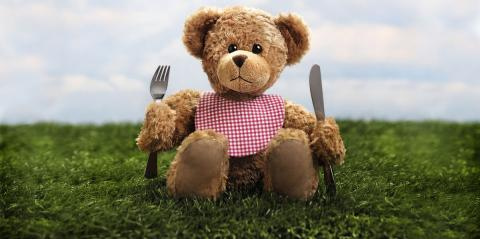 A teddybear sitting in the grass armed with a fork and a knife