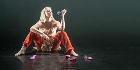 a woman sitting on stage, examining a high-heeled Barbie shoe
