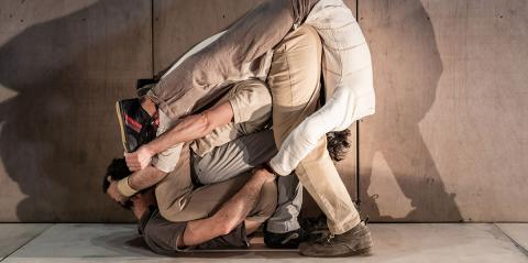 a pile on men in beige clothes stacked on top of each other