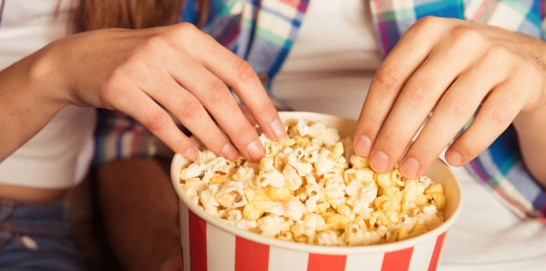 A couple's hands are reaching into a red and white striped container of popcorn