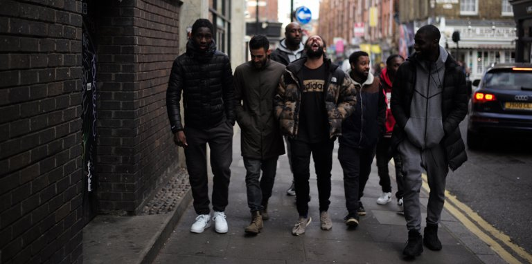 7 men walking together in the street, one member of the group has his head thrown back, laughing