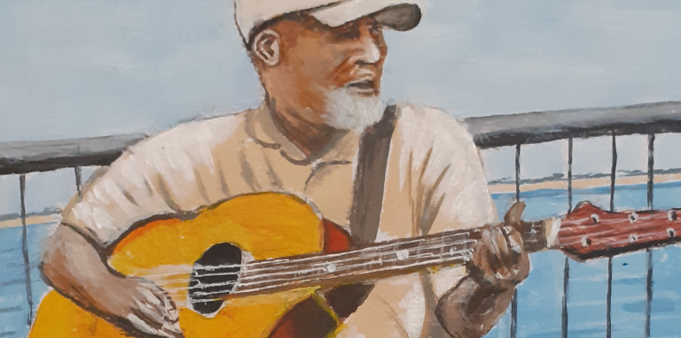 a man with a guitar by the sea