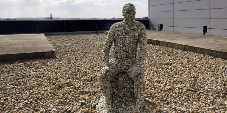 life size sculpture of seated man made of pebbles