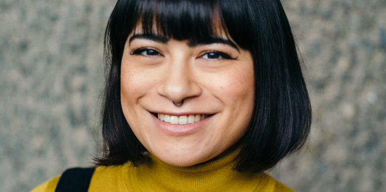 a woman with black hair and a fringe smiling