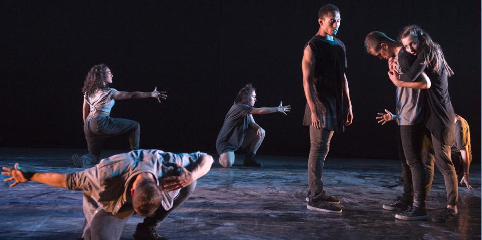 201 Dance: a group of performers, some kneeling, some reaching out, some hugging in diffuse stage lighting