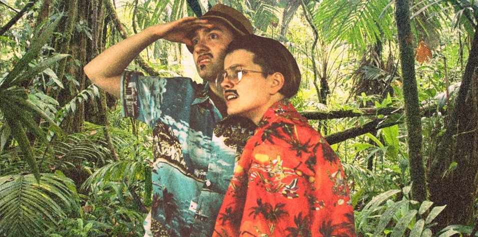 two women dressed as men with moustaches and colourful Hawaii shirts stand in a jungle, looking confused