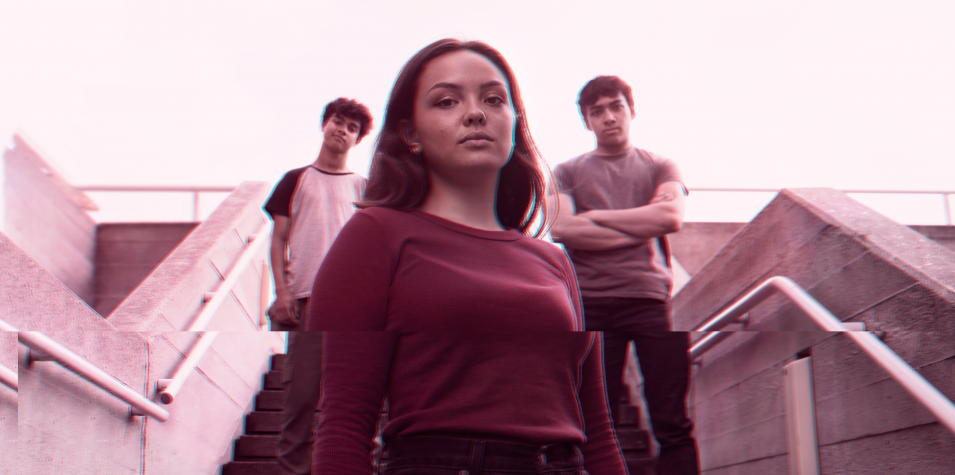 three young people standing looking at the camera. image has a pink filter.