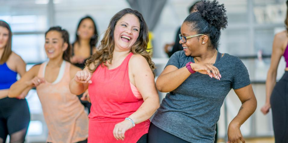 artsdepot classes: two women in sports wear laugh brightly and bump their hips together