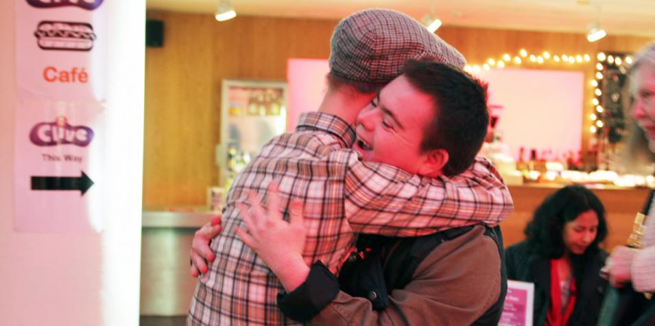 photo of two people hugging at artsdepot