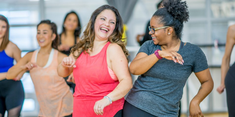 Two women in a dance studio. They wear sportswear, are smiling and bumping their hips together.