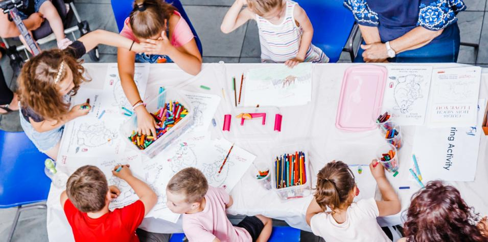 a group of children sitting around a drawing table filled with crayons and drawing sheets