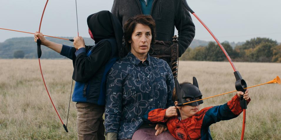 Edith Tankus: a picture taken outside where there is grass all around them. three people, an adult and two children sit down, both children are shooting bow and arrows and the woman is centre looking at camera