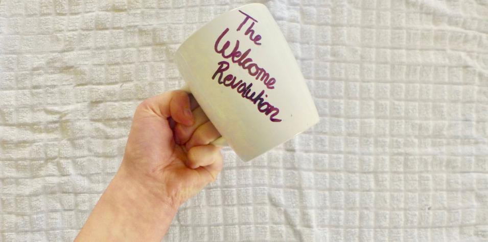 A raised fist holding a mug, writing on the mug reads The Welcome Revolution