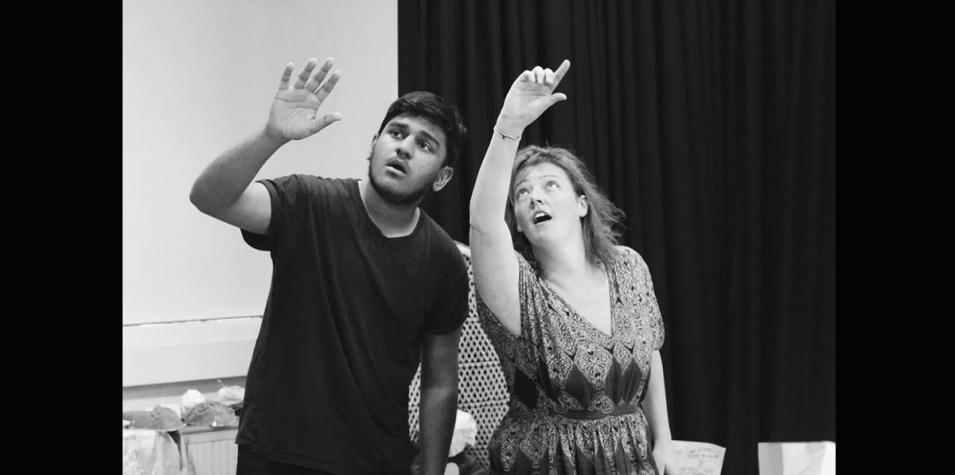 Two members of Handprint Theatre in a rehearsal room, pointing upwards