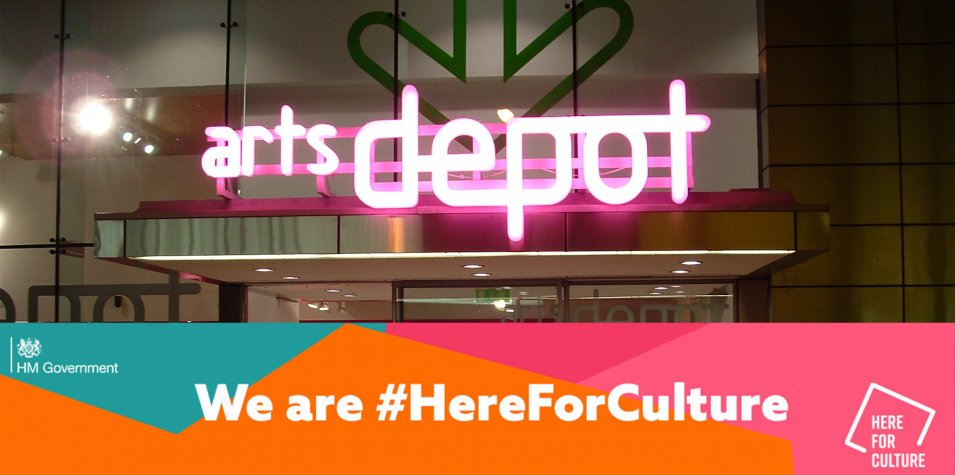 An image of the outside of artsdepot, taken at night. The neon pink artsdepot sign is glowing. At the bottom of the image is a multi coloured band with #HereForCulture written on it