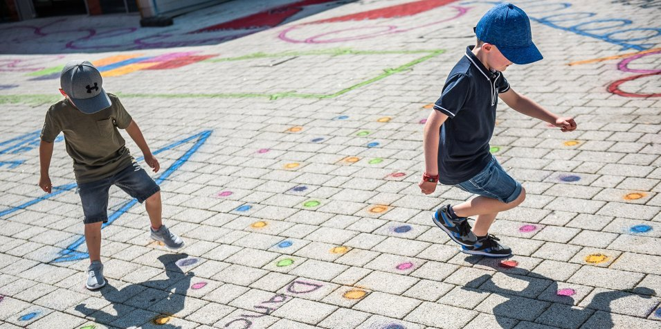 Two boys wearing shorts, t-shirts and caps are playing outside. A large area of paved ground can be seen, and every inch of it is covered in brightly coloured dots, lines and squiggles for the boys to follow.