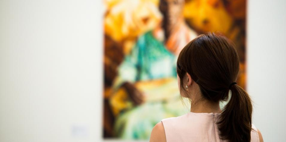 the back of a women with a pony tail in a sleeve less dress, in a wide space with a colourful painting visible in the background