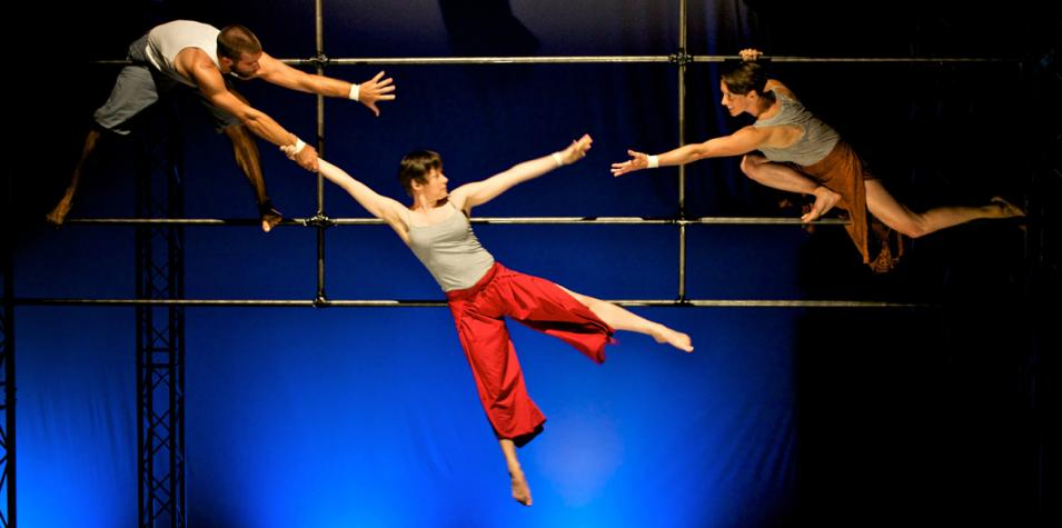 Three performers suspended from an aerial framework
