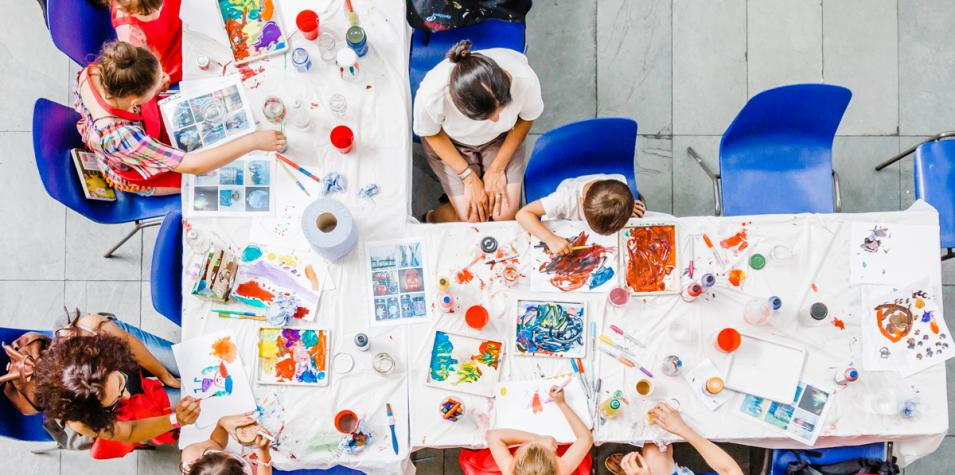 a view from above onto a table laden with paint and half-finished paintings, children and parents sitting around the table painting together