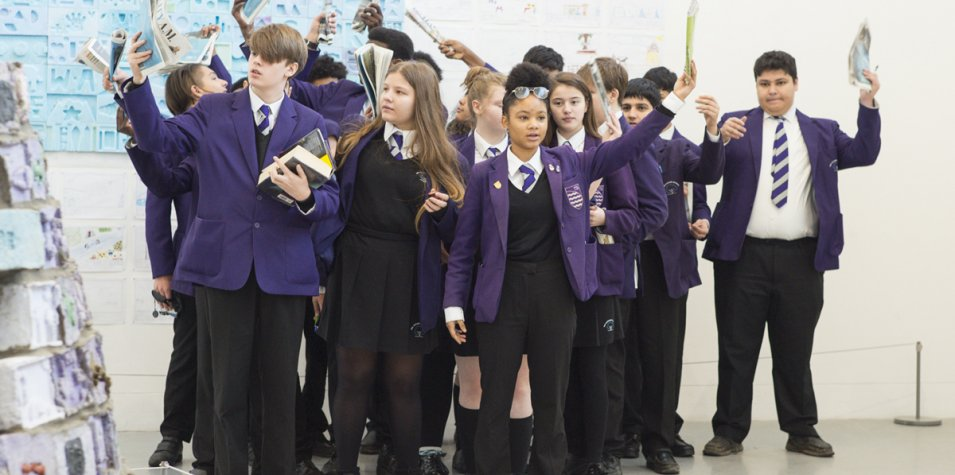 A group of children in purple and black school uniforms stand in a huddle, waving newspapers. They're standing in a gallery space, with a large clay wall installation visible behind them
