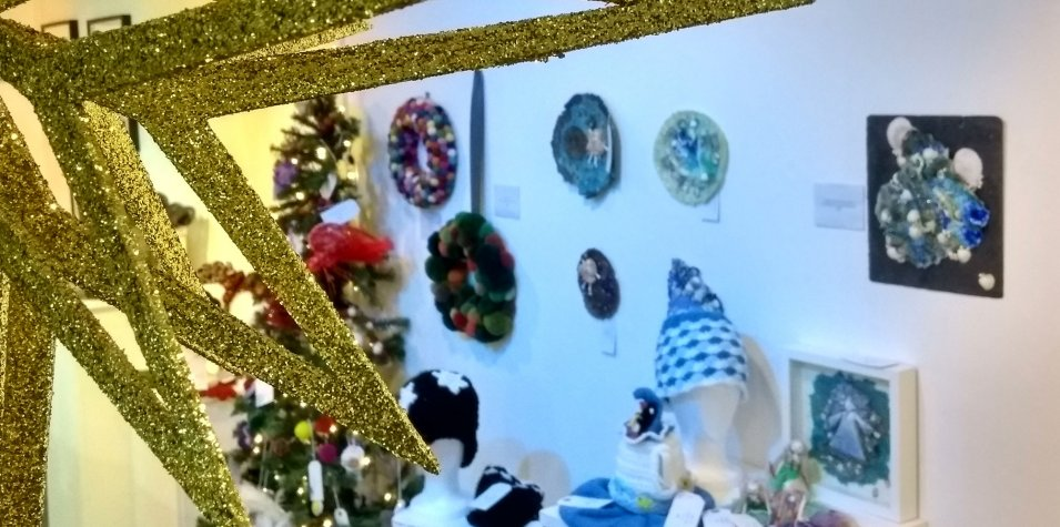 Winter Showcase: a close up of a golden glittering star ornament, behind which knitted clothing and artwork is exhibited along a white wall