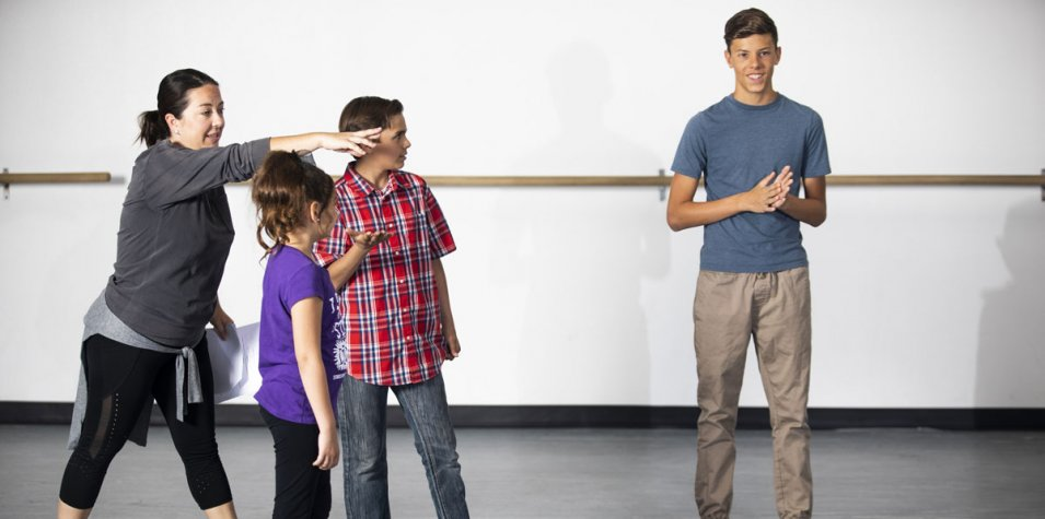 A director talks to a group of young performers in a studio