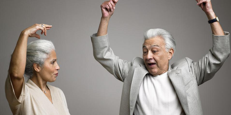A woman and a men with grey hair with their hands in the air