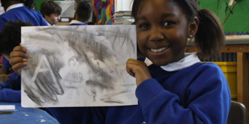 Primary school pupil holding artwork