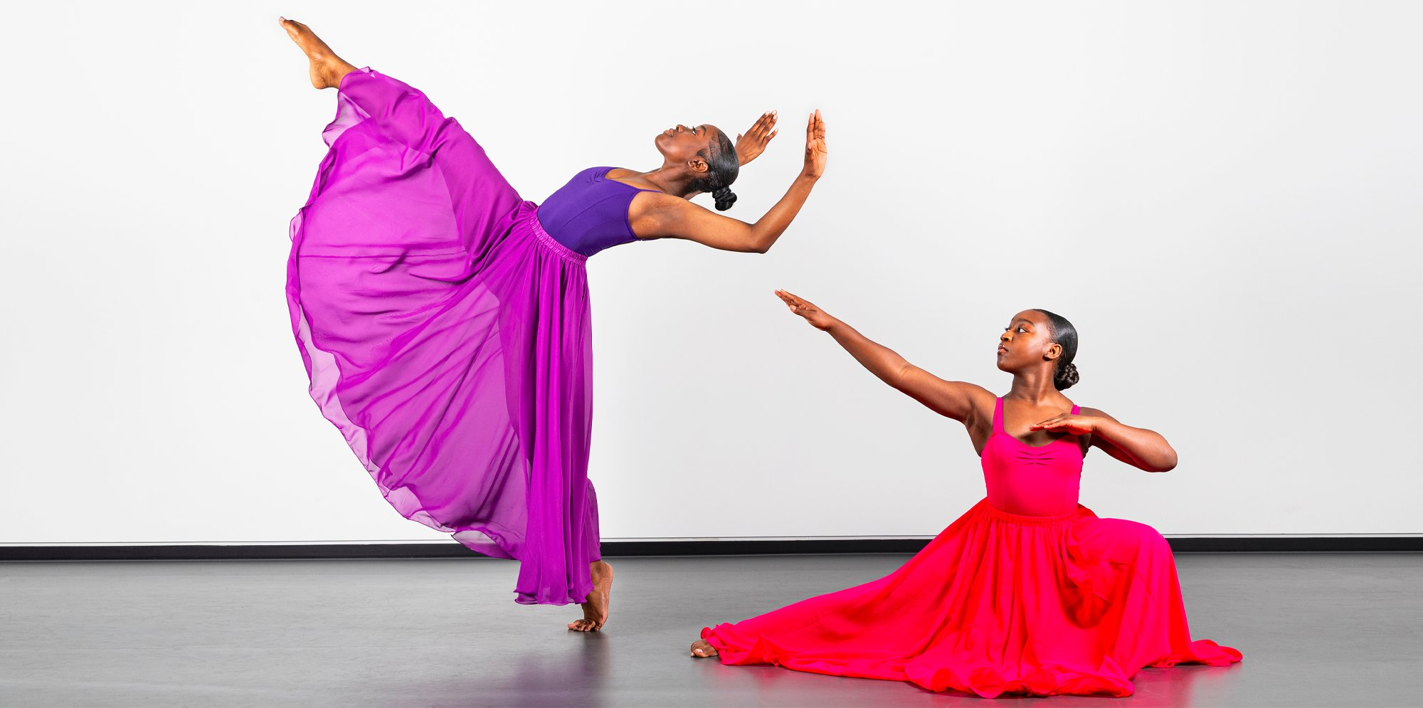 An image of two dancers, one in a purple dress has one leg up and arches her back in a graceful pose, the other in a pink dress sits on the ground and points her arms strikingly towards the other dancer