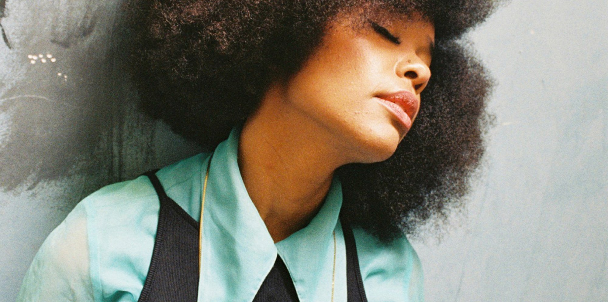 Abimaro: a young black woman with afro hair leans against a gray wall, her eyes are closed. She is wearing a a green blouse with big lapels, a black tank top over the blouse and a thin gold necklace.