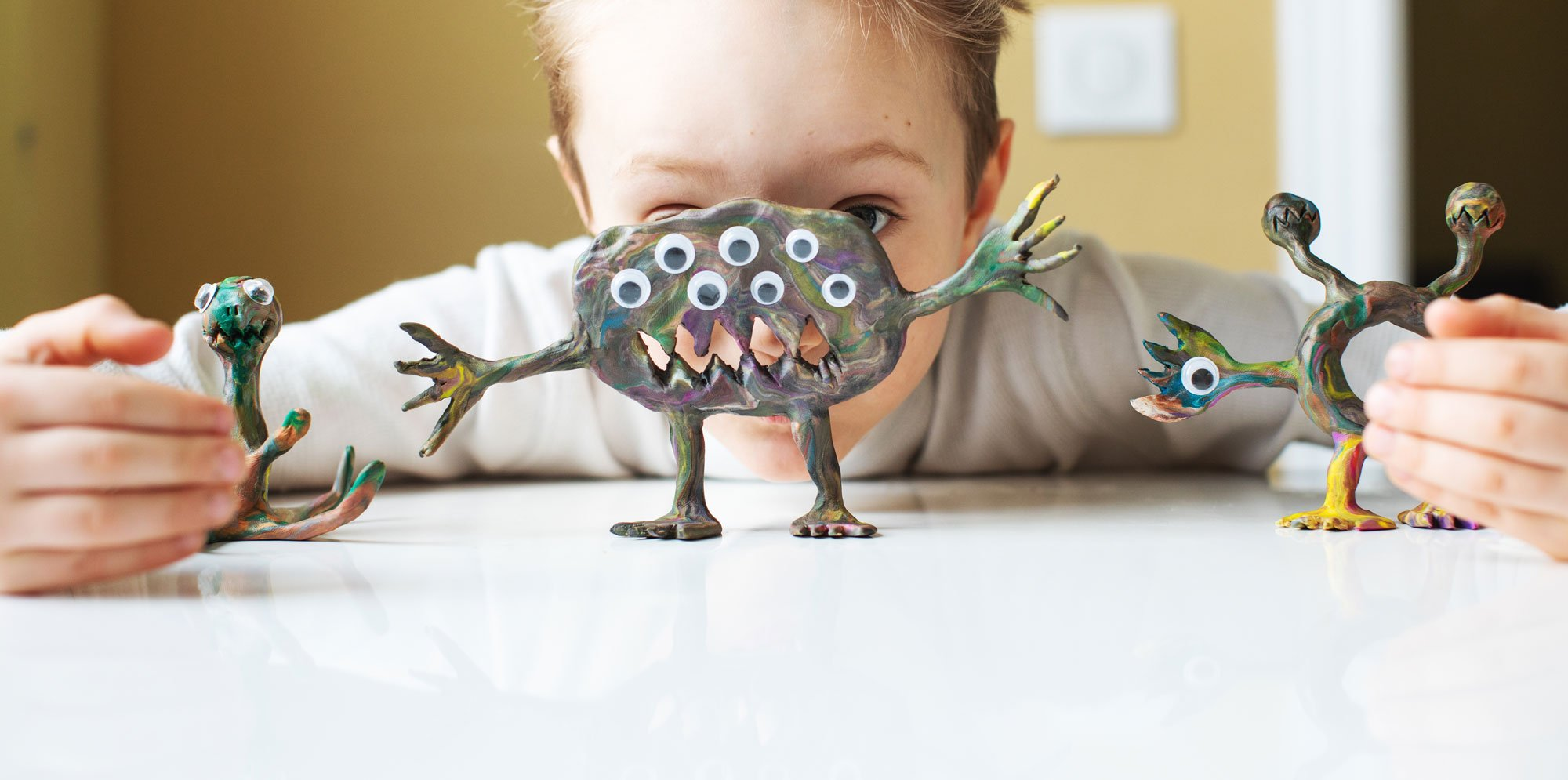 AniMates: a boy hiding behind little monsters made from clay with a number of goggly eyes