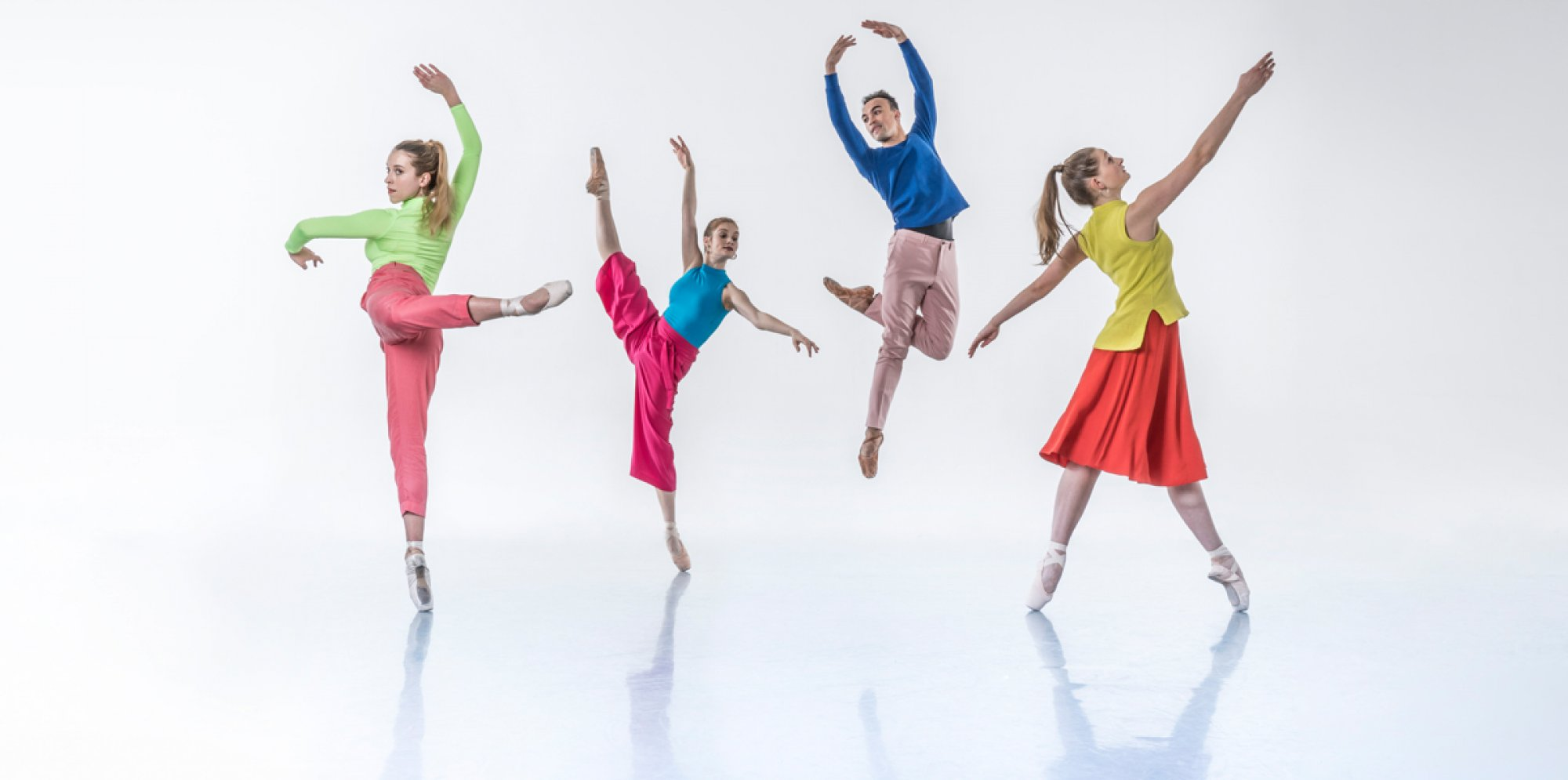Images Ballet: four dancers in colourful clothes in mid-jump. Photo credit Johan Persson