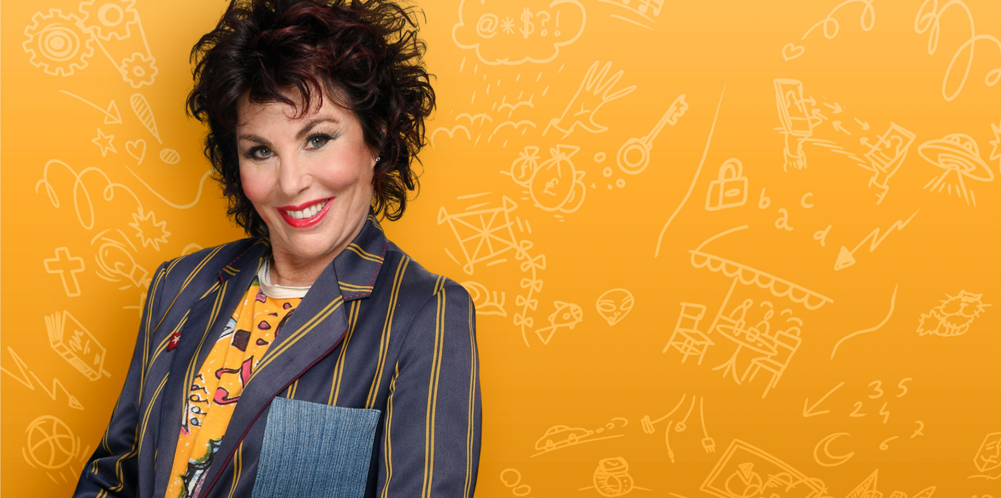 Ruby Wax smiling on an orange background